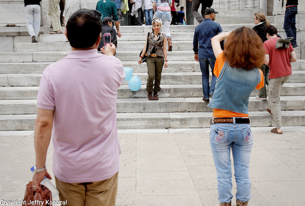 A women poses for a photo on the steps of the Blue Mousqe in Istanbul, Turkey