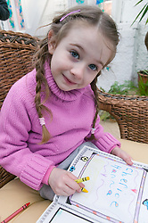 Little girl drawing with crayons in a book,