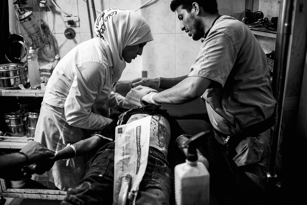 Syria, Aleppo, 2012/10/09.<br /> Inside Dar Al-Shifaa hospital.<br /> Nurses are trying to save the life of a child head wounded by a mortar fragments.