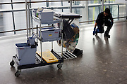 With trolley nearby, a cleaner stoops to remove sticky debris on the concourse floor at Heathrow Airport's Terminal 5.