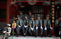 epa02776363 A Chinese boy sits among Beijing security officers before an event at a park in Beijing, China on 12 June 2011.  EPA/HOW HWEE YOUNG