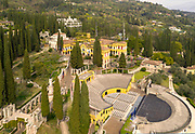La Prioria, home of Gabriele D'Annunzio, 1863-1938, Italian writer, soldier and fascist, and Amphitheatre, aerial view, at Vittoriale degli italiani, or The Shrine of Italian Victories, his estate and museums at Gardone Riviera, Lake Garda, Brescia, Lombardy, Italy. The house was originally the Villa Cargnacco, which was rebuilt by Gian Carlo Maroni from 1922 and developed until 1955. The amphitheatre, or Parlaggio, was begun in 1931 and is used for concerts, seating 1500. The estate consists of the Prioria, where d'Annunzio lived 1922-38, an amphitheatre, the protected cruiser Puglia, the MAS vessel used by D'Annunzio in 1918 and a mausoleum. It is part of the Grandi Giardini Italiani. Picture by Manuel Cohen
