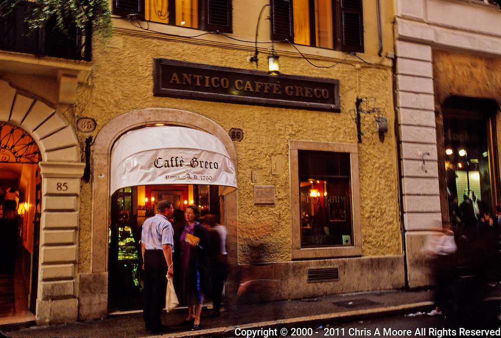 Two people have a conversation outside the Caffe Greco in Rome.  Meanwhile life goes on as seen by the ghostly images of people passing by them.  The streets are wet from a rain storm.  The lights glow our from the caffe as the color of twilight reflects off of the buildings.