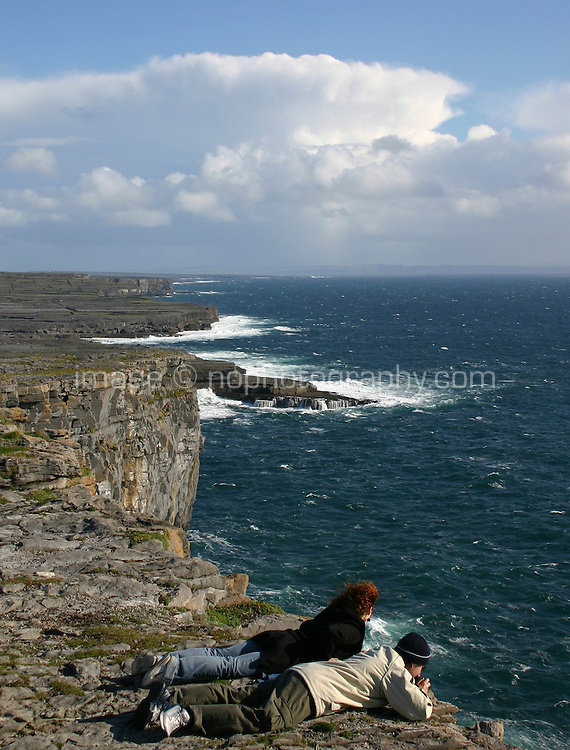 Tourists looking over the cliffs at Dun Aonghus fort, Inis Mor the Aran Islands, Connemara, County Galway, Ireland.