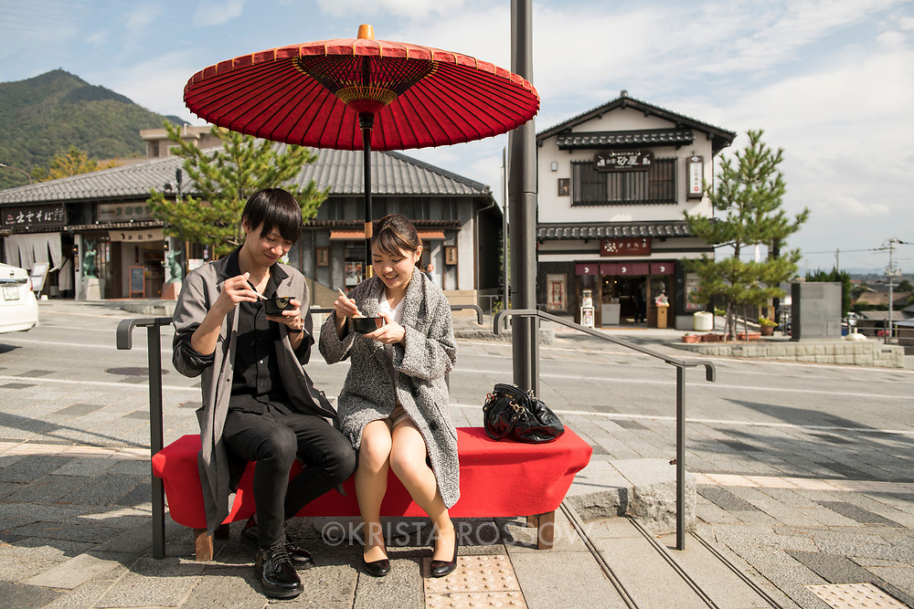 A young Japanese couple (model released) sits outside of a food stall near the entrance to the Izumo-Taisha Grand Shrine. The road leading to Izumo-Taisha Grand Shrine is lined with shops, eateries, trees, and sacred torii gates. Shimane Prefecture, Japan,
