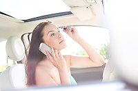 Young woman using mobile phone while applying mascara in car