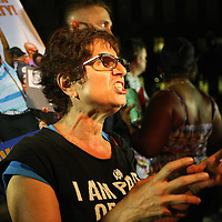 A lady reacts to the not guilty verdict in the George Zimmerman murder trial at the Seminole County Courthouse on Saturday, July 13, 2013, in Sanford, Florida.  Zimmerman had been charged for the 2012 shooting death of Trayvon Martin and was found not guilty by a jury of six women. The protests on the grounds ended peacefully after the verdict was read. (AP Photo/Alex Menendez)