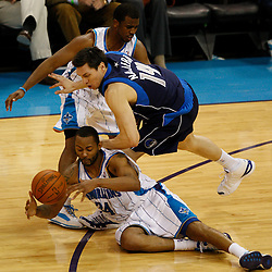 Mar 22, 2010; New Orleans, LA, USA; New Orleans Hornets guard Morris Peterson (24) and guard Chris Paul (3) scramble for a loose ball with Dallas Mavericks forward Eduardo Najera (14) during the second half at the New Orleans Arena. The Hornets defeated the Mavericks 115-99. Mandatory Credit: Derick E. Hingle-US PRESSWIRE