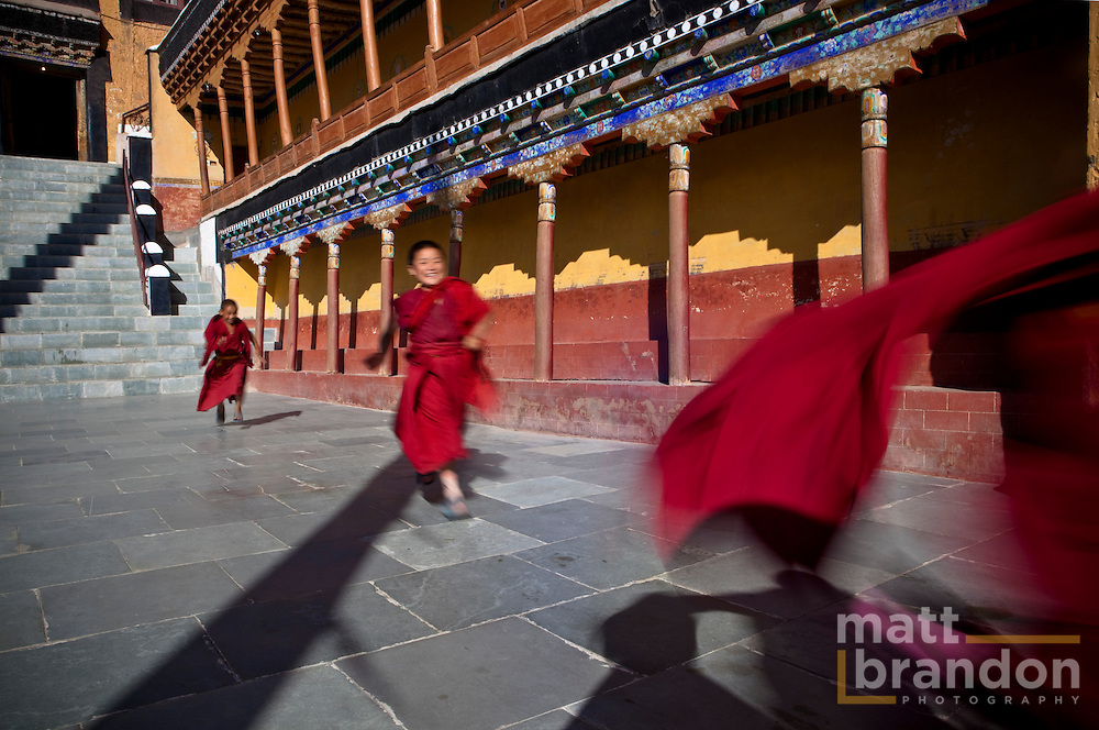 Child monks run to play after morning prayers in Tiksey monastery.