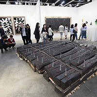 Visitors look artist Chen Zhen's 'Le Chemin / Le Radeau de l'écriture, 1991' at Art Basel Hong Kong 2017 on 23 March 2017, in Hong Kong Convention and Exhibition Centre, Hong Kong, China. Photo by Chris Wong / studioEAST