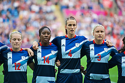 COVENTRY, ENGLAND - Friday, August 3, 2012: Great Britain's Kim Little, Anita Asante, Jill Scott and Stephanie Houghton line-up for the national anthem before the Women's Football Quarter-Final match between Great Britain and Canada, on Day 7 of the London 2012 Olympic Games at the Rioch Arena. Canada won 2-0. (Photo by David Rawcliffe/Propaganda)