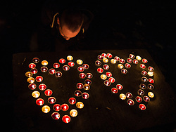 "© Licensed to London News Pictures . 01/12/2013 . Manchester , UK . A man kneels and bows his head in front of candles arranged in the shape of two hearts . World AIDS Day commemoration in Sackville Park , Manchester , this evening (Sunday 1st December 2013) including a candle-lit procession around the city's "" Gay Village "" . Photo credit : Joel Goodman/LNP"