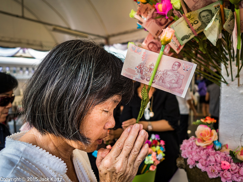 14 DECEMBER 2015 - BANGKOK, THAILAND: A woman prays and donates money to the temple before the start of the  Supreme Patriarch's funeral at Wat Bowon Niwet in Bangkok. Somdet Phra Nyanasamvara, who headed Thailand's order of Buddhist monks for more than two decades and was known as the Supreme Patriarch, died Oct. 24, 2013, at a hospital in Bangkok. He was 100. He was ordained as a Buddhist monk in 1933 and appointed as the Supreme Patriarch in 1989. He was the spiritual advisor to Bhumibol Adulyadej, the King of Thailand when the King served as a monk in 1956. His funeral, which will take three days,   Dec. 15-17, will be attended by thousands of Thais and most of the Royal Family. Buddhist clergy from around the world are expected to attend.       PHOTO BY JACK KURTZ