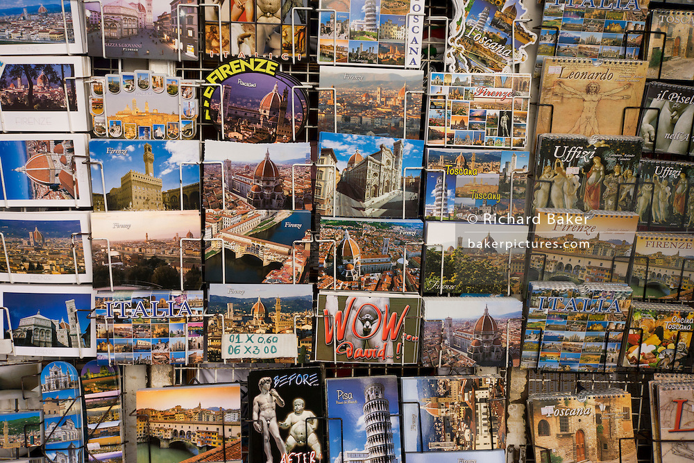 Dozens of Florence postcards are seen on a rack in Piazza Santa Giovanni beneath Florence's Santa Maria del Fiore (Duomo) Cathedral. Various views of theis city's landscapes and scenes are seen: The Duomo cathedral; Brunelleschi's Dome; Michelangelo's David statue; renaissance paintings in the Uffizi, the Ponte Vecchio and even the Leaning Tower of Pisa are all represented here - proof that the postcard is still a memento that tourists who come to foreign cities still currently wish to send friends and relatives, in the digital age.