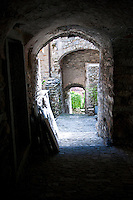 Ticino, Southern Switzerland. Verdasio.  Stone passageway - dimly lit - leading through courtyards and buildings.