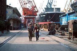 CHINA SHANGHAI NOV01 - Two shipyard workers walk along the quay occupied by large ocean-going vessels.. . jre/Photo by Jiri Rezac. . © Jiri Rezac 2001. . Contact: +44 (0) 7050 110 417. Mobile:  +44 (0) 7801 337 683. Office:  +44 (0) 20 8968 9635. . Email:   jiri@jirirezac.com. Web:     www.jirirezac.com