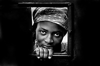 A Cite Soleil resident peers through an opening in the gate to the hospital with hopes of getting someone inside to look at her sick baby.