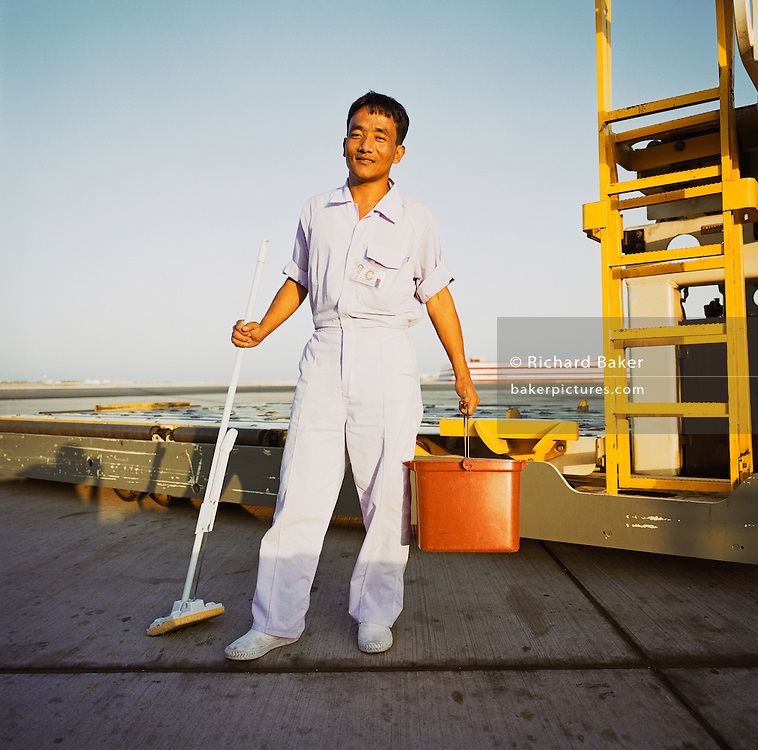 An aircraft cleaner from Kathmandu, Nepal, stands in white overalls with his bucket and mop on the tarmac at Bahrain International airport. It is another hot day in this key hub airport in this Gulf region, providing a gateway to the Northern Gulf. The airport is the major hub for Gulf Air which provides 52% of overall movements and is also the half-way point between Western Europe and Asian destinations such as Hong Kong and Beijing. Gulf states also rely on the workforces from south-Asia such as India, Pakistan, Sri Lanka and Bangladesh whose wages are often low and harsh living conditions compared to local nationals and tourists who enjoy superior accommodation. Picture from the 'Plane Pictures' project, a celebration of aviation aesthetics and flying culture, 100 years after the Wright brothers first 12 seconds/120 feet powered flight at Kitty Hawk,1903.  .