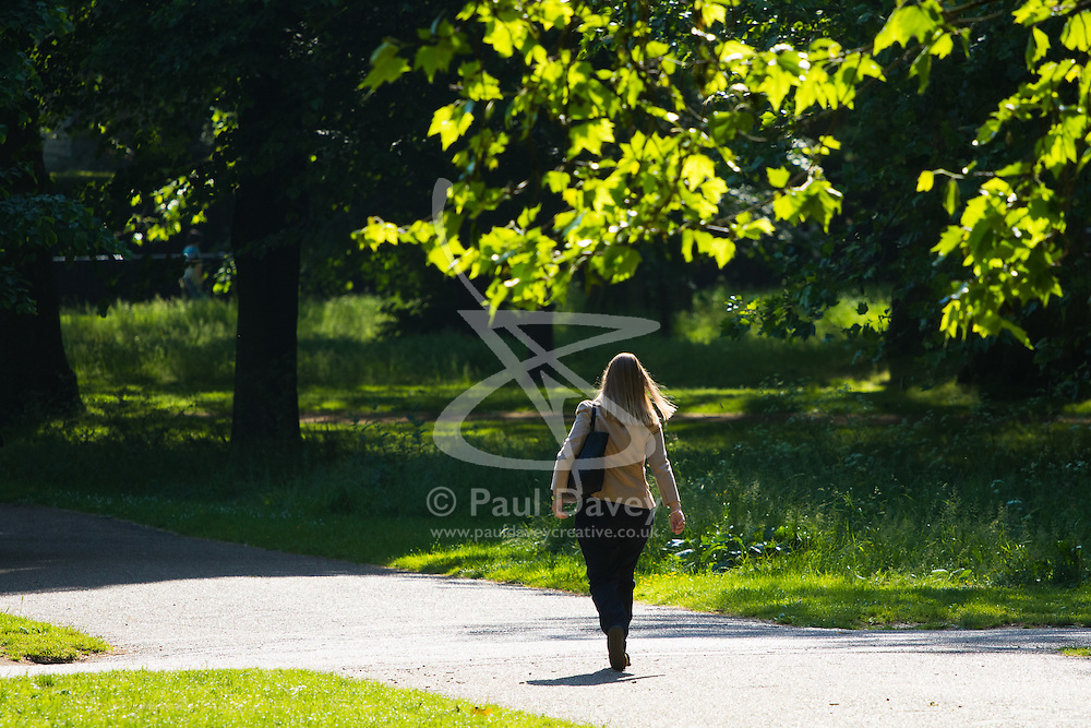 Green Park, London, June 6th 2016. A woman walks through the dappled sunshine in London's Green Park as weather forecasters predict temperatures for London to be in the mid-twenties.