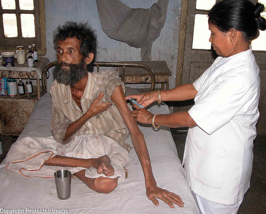 A nurse is giving injection to S. Bhattcharjee, a TB patient at Government TB Hospital at Guwahati, capital of Northeastern Indian state of Assam, Wednesday, March 23, 2005. More than one lakh people are infected TB germs or suffering TB virus in Northeast India, while the world will observe 24th March as World TB Day, claims the Health department of India. (AFP Photo/Shib Shankar Chatterjee)