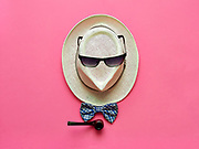 Smoking pipe and bowtie lying near straw hat with sunglasses on pink background