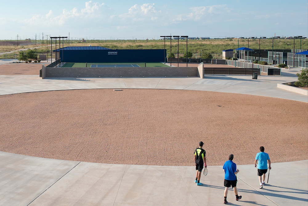 Three visitors walk to the courts at the Bush Tennis Center in Midland, Texas on August 12, 2014. (Cooper Neill for The New York Times)