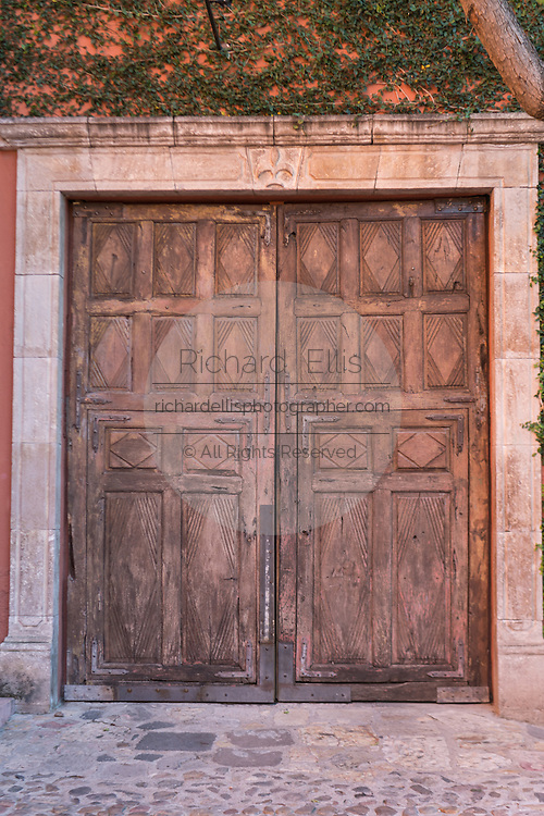 A colonial style wooden door at the plaza de San Felipe Neri in San Miguel de Allende, Mexico.