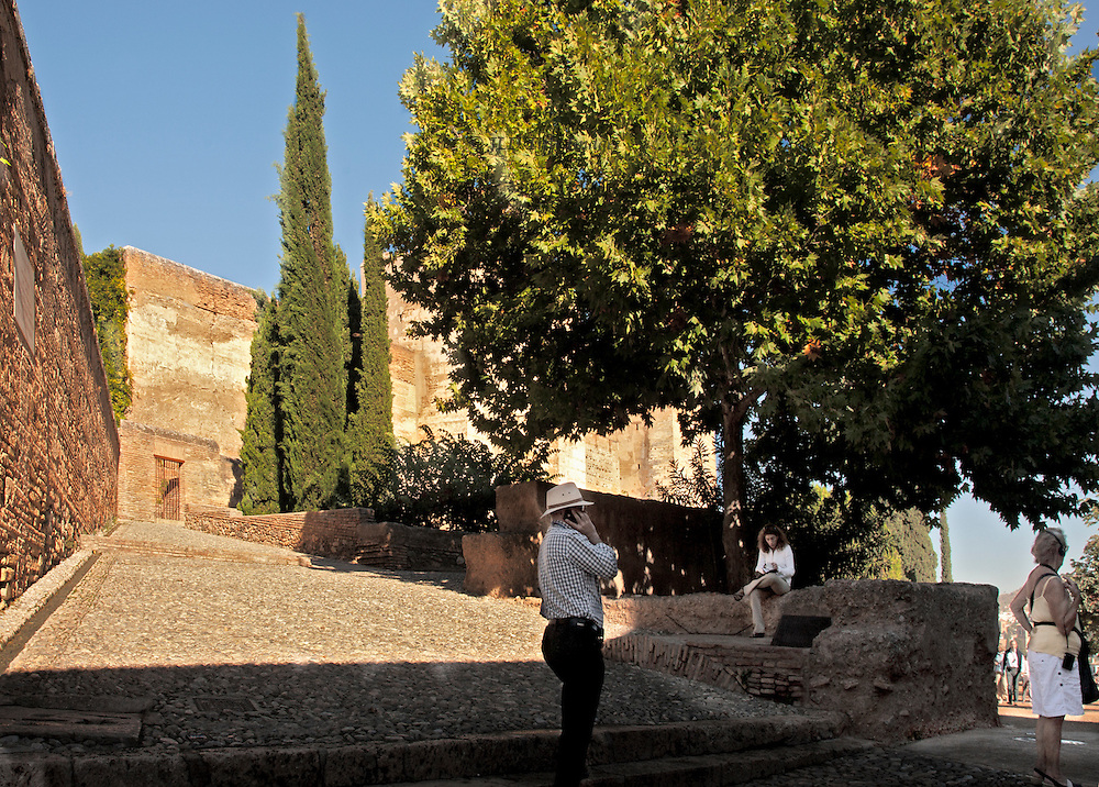 Plaza of Cisterns in the Alhambra, empty except for three people: woman seeming to be waiting for someone, a young woman seated and reading, and a man in a straw hat using his mobile telephone.  Sunlit cobbled ramp and walls, punctuated by cypress trees.  Elsewhere there were floods of European and Japanese tourists
