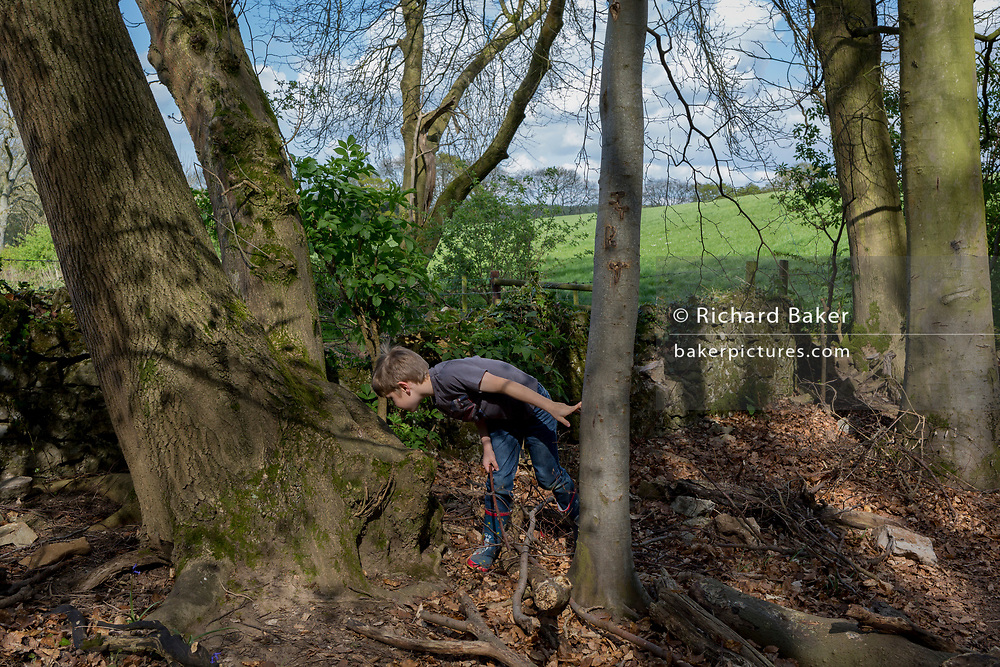 A seven year-old boy in woods plays in woods, on 23rd April 2017, in Wrington, North Somerset, England.