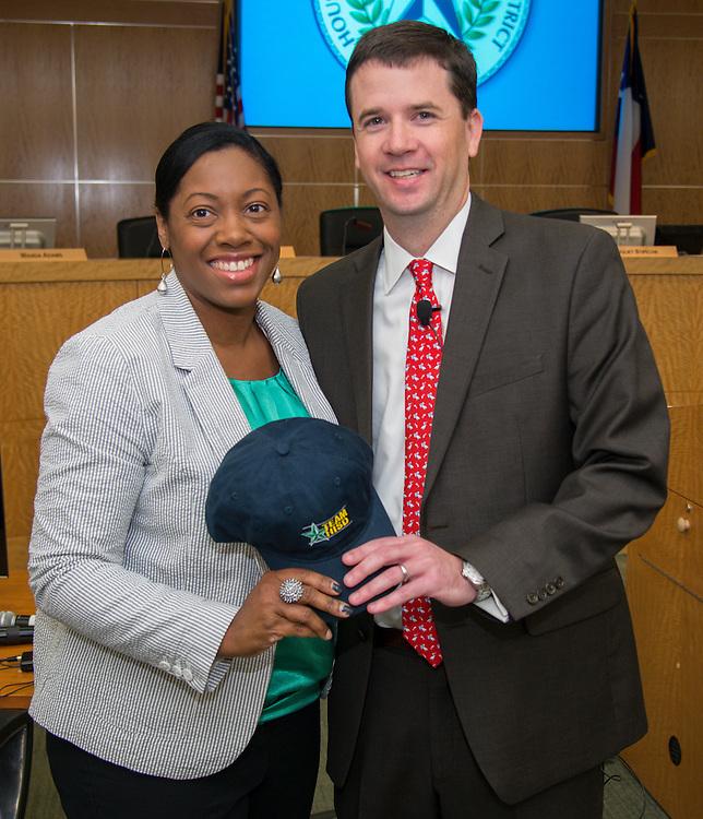 Dr. Andrew Houlihan, right, presents Washington High School principal LaShonda Bilbo-Ervin, left, with a Team HISD cap, June 11, 2014.