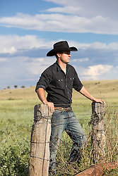 All American cowboy on a ranch at sunset