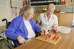 Occupational therapist with patient playing solitaire which is a grip and release task promoting upper limb function after stroke,