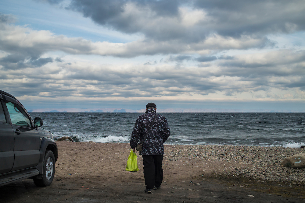 A man walks on the shore of Lake Baikal on Sunday, October 20, 2013 in Baikalsk, Russia.