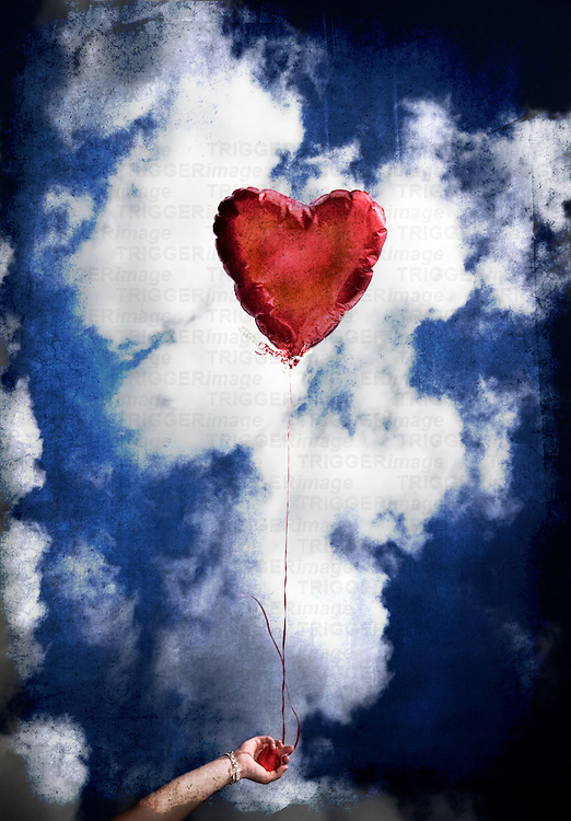 A girl holds a red balloon shaped liked a heart against the blue sky