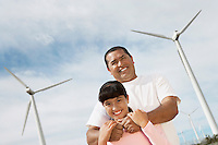 Father embracing daughter (7-9) at wind farm, portrait