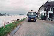 Nederland, Ooij, 01-02-1995Eind januari, begin februari 1995 steeg het water van de Rijn, Maas en Waal tot record hoogte van 16,64 m. bij Lobith. Een evacuatie van 250.000 mensen was noodzakelijk vanwege het gevaar voor dijkdoorbraak en overstroming. op verschillende zwakke punten werd geprobeerd de dijken te versterken met zandzakken. Hier in de Ooijpolder bij Nijmegen patrouilleert de politie langs de lege huizen.Late January, early February 1995 increased the water of the Rhine, Maas and Waal to a record high of 16.64 meters at Lobith. An evacuation of 250,000 people was needed because of flood risk. At several points people tried to reinforce the dikes with sandbags. Here in the Ooijpolder in Nijmegen.Foto: Flip Franssen/Hollandse Hoogte