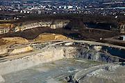 Nederland, Limburg, Maastricht, 07-03-2010; Sint-Pietersberg, mergelgroeve voor de winning van mergel (eigenlijk kalksteen) in dagbouw door cementfabriek ENCI. Wat er nog resteert van de St.Pietersberg is beschermd natuurgebied en bovengronds en ondergronds aangewezen als beschermd Habitatrichtlijngebied. Nieuwbouwwijk van Maastricht in de achtergrond..Marl quarry for the extraction of marl (limestone actually) in surface mining by cement factory ENCI. What is left of the Sint-Pietersberg is designated as protected area, both on groundlvel and underground the habitat directives apply..luchtfoto (toeslag), aerial photo (additional fee required);.foto/photo Siebe Swart
