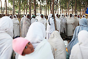 """Worshippers gather during a ceremony blessed the water they brought in bottles. Occupying a high plateau and bordering with Eritrea in the very north of Ethiopia lies the ancient Province of Tigray. It is an area widely considered to be the fulcrum of Ethiopian culture with towns dated to before the birth of Christ. Distinctively different from the rest of Ethiopia, strongly Orthodox Christian and culturally proud, Tigray is a mountainous and rocky region dotted with ancient churches carved in to sandstone cliffs. Filling these churches are old religious manuscripts and Bibles safe-guarded by protective Priests. Its remoteness has protected the culture as well as the religious sanctuaries that have been described as """"the greatest of the historical-cultural heritages of the Ethiopian people"""". But now Tigray is at a crossroads. Improved infrastructure has led to an opening up of even the remotest towns and villages. Signs of modernity such as internet cafes and cell phones are increasingly being used by younger Tigraians dressed in jeans and T-shirts. Yet the Church remains an ancient and powerful institution which protects its ancient customs creating scenes that haven't changed since Biblical times.."""