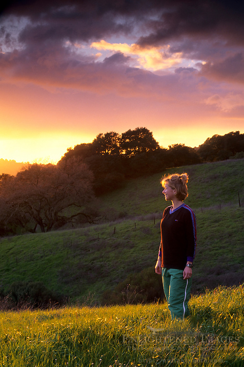 Female hiker at sunset in the hills of Briones Regional Park, above Lafayette Contra Costa County, CALIFORNIA