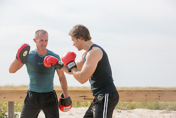 coach and a man with boxing gloves outdoors working out