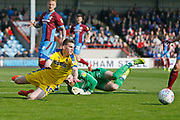 Wimbledon midfielder Steve Seddon (15) goes down under a challenge from Scunthorpe United goalkeeper Jak Alnwick (25)  during the EFL Sky Bet League 1 match between Scunthorpe United and AFC Wimbledon at Glanford Park, Scunthorpe, England on 30 March 2019.