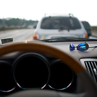 A pair of Costa del Mar sunglasses resting on the dashboard of a Lexus RX350 SUV while the driver waits in traffic as a draw bridge stops traffic to open its span