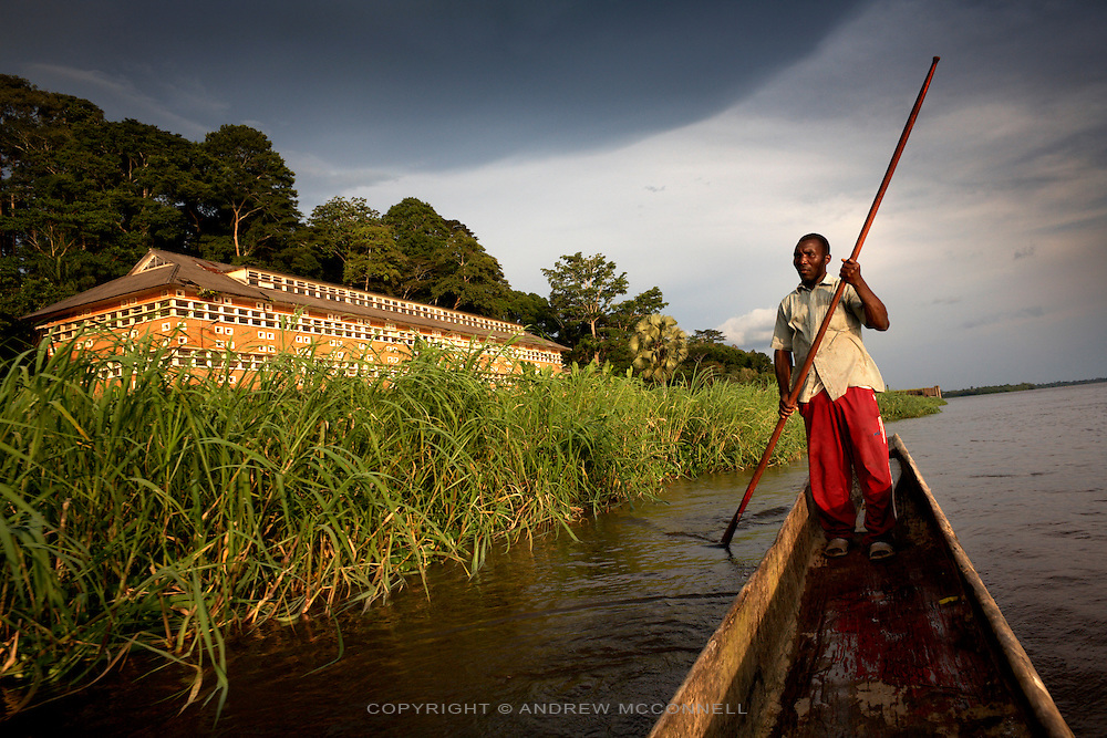 A man navigates his pirogue along the Congo  river past the Yangambi Research Station in, Yangambi, DR Congo, on Saturday Dec. 6, 2008. The largest building in Yangambi faces the riverfront and was perviously a maintenance centre and repair garage for the entire facility. It now lies abandoned and derelict..Yangambi Research Station is the former Belgian headquarters for all major scientific ecological, biological and agricultural research in Africa between the 1930's and 1960. It stretches for 33 km inland from the river and contains 250 residential houses and many research buildings and offices, including a herbarium and library. At it's height approximately 250 scientists and 500 technicians were based here along with 1000 more Belgian workers ranging from doctors to bricklayers. With the families and constant visitors to the station included the total population would have ranged in the several thousands. Abandonment began in 1960 with independence and although Congo attempted to maintain Yangambi, sometimes in co-operation with the Belgians, the facility began to fall into disrepair through the 70's and 80's. War in the 1990's halted all potential for progress and for the past decade a skeleton crew has made a futile attempt to stave off further decline.