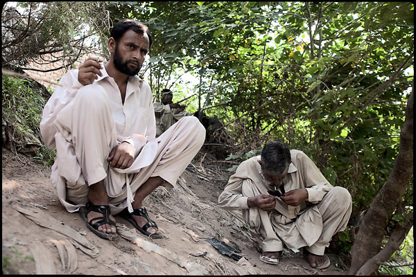 """Heroin smokers, belonging from the working class, consume their dose of drug nearby a polluted river. Islamabad Pakistan, on friday, August 29 2008.....""""Pakistan is one of the countries hardest hits by the narcotics abuse into the world, during the last years it is facing a dramatic crisis as it regards the heroin consumption. The Unodc (United Nations Office on Drugs and Crime) has reported a conspicuous decline in heroin production in Southeast Asia, while damage to a big expansion in Southwest Asia. Pakistan falls under the Golden Crescent, which is one of the two major illicit opium producing centres in Asia, situated in the mountain area at the borderline between Iran, Afghanistan and Pakistan itself. .During the last 20 years drug trafficking is flourishing in the Country. It is the key transit point for Afghan drugs, including heroin, opium, morphine, and hashish, bound for Western countries, the Arab states of the Persian Gulf and Africa..Hashish and heroin seem to be the preferred drugs prevalence among males in the age bracket of 15-45 years, women comprise only 3%. More then 5% of whole country's population (constituted by around 170 milion individuals),  are regular heroin users, this abuse is conspicuous as more of an urban phenomenon. The substance is usually smoked or the smoke is inhaled, while small number of injection cases have begun to emerge in some few areas..Statistics say, drug addicts have six years of education. Heroin has been identified as the drug predominantly responsible for creating unrest in the society."""""""