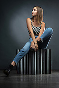 Houston fashion model Hannah Pressley in jeans and checkerboard top posing on striped cube by Gerard Harrison, fashion photographer.