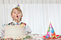 Young birthday boy blowing candles on cake