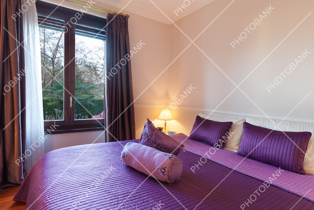 bedroom of a modern apartment, double bed with purple bedspread
