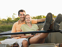 Couple sitting in jeep woman leaning legs up