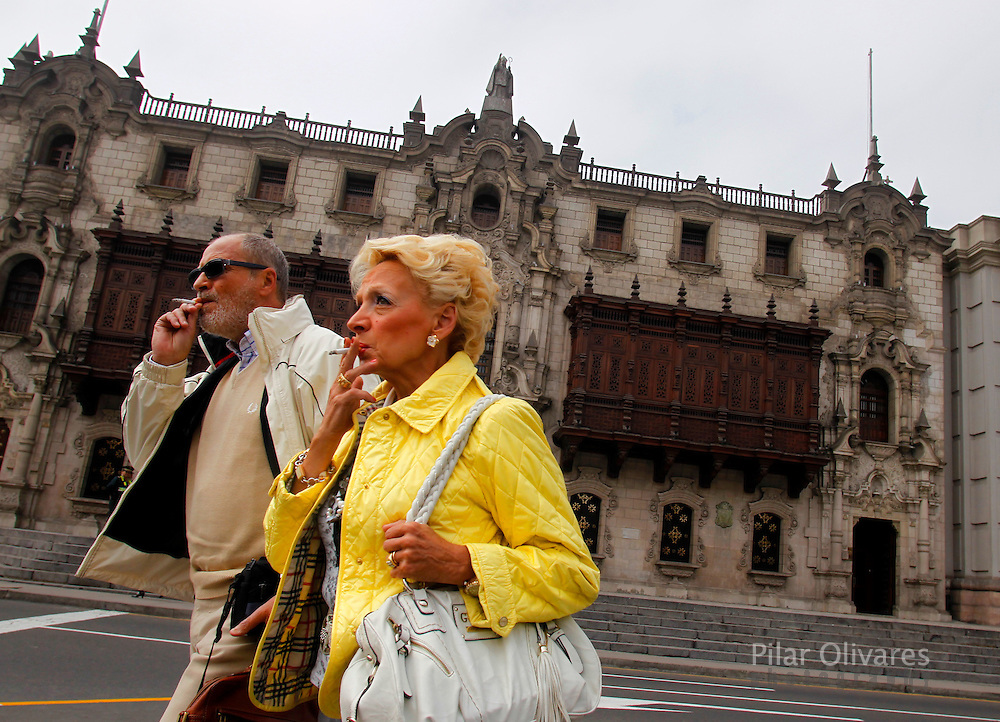 Tourists smoking cigars walk in front of the Cathedral of Lima in downtown. Photo by Pilar Olivares