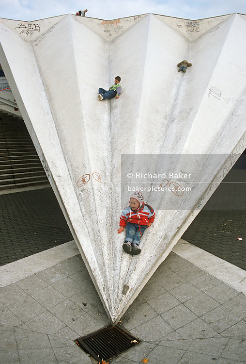 Children play on an East Berlin shopping precinct roof built during the Communist DDR-era - Alexanderplatz.